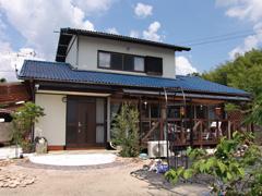青い屋根が印象的な外観です 整えばバラのアーチもできます